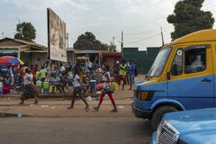 Street scene in the city of Bissau with a woman exiting a mini bus toca toca at the Bandim Market, in Guinea-Bissau. Bissau, Republic of Guinea-Bissau - January Stock Photo