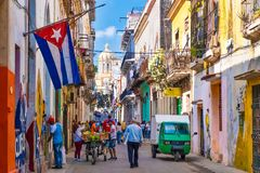 Street scene with cuban flag on a colorful street in Old Havana. With a view of the Presidential Palace royalty free stock photography