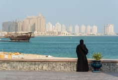 Street scene in Doha, Qatar with lady wearing traditional Qatari black dress and head cover. With the Pearl district skyscrapers in the background royalty free stock image