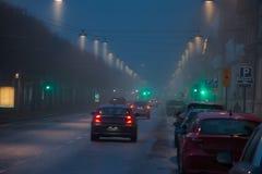 Street scene with evening fog. Foggy evening in the city Stock Photos