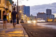 Street scene in Havana on the Malecon  at sunset. Street scene in Havana on the Malecon seaside avenue at sunset Stock Photo