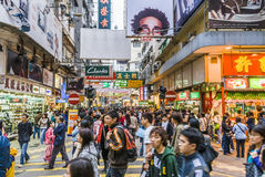 Street scene in Hong Kong at night. Pedestrian zone in Hong Kong, China with multitude of people walking and strolling and illuminated shops and ads Royalty Free Stock Image