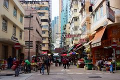 Street scene in Hong Kong: skyscrapers, people, market, signage Royalty Free Stock Photo