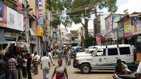 Street scene in Madurai, India. A busy street in Madurai india, with people, motorcycles, and vans Stock Photo