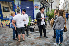 Street scene in Marais with Orthodox Jewish young men talking with tourists Royalty Free Stock Photography