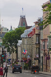 Street scene on Old Quebec city. Street of Old Quebec city with historic buildings, carriage, restaurants, pedestrians, tourists and top of Parliament building Royalty Free Stock Photo