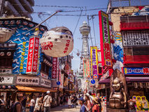 A street scene in Osaka showing the famous Tsutenkaku Tower. A street scene showing the famous Tsutenkaku Tower in Osaka, Japan. Also visible are colourful Royalty Free Stock Photography