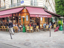 Street Scene in Paris. People are dining outside on the patio of les philosophes on a summer day Royalty Free Stock Images