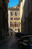Street scene in Rome. Close street, parking cars and a sonny facade stock image