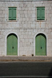 Street scene - stone wall with green doors and windows Stock Images
