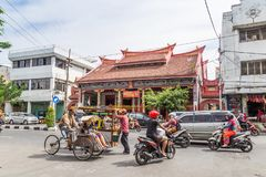Street scene in Surabaya Indonesia. Surabaya, Indonesia - November, 04, 2017:  Street view with Chinese temple, bicycle taxi and other trafiic in in Surabaya Royalty Free Stock Images