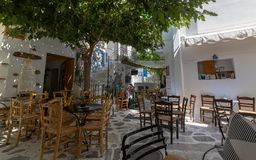 Street scene with tavernas and square, on aegean island of Tinos, Greece. Part of a square with public seating on the aegean island of Tinos, in Cyclades royalty free stock photo