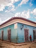 Street scene in trinidad. A blue house in a cobblestone street with a man passing by in cuba, trinidad Stock Images