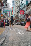 Street scene typically Asian in Hong Kong. HONG KONG, ASIA - AUGUST 2, 2017; People cross street in scene typically Asian with plethora neon signs in Hong Kong Royalty Free Stock Photo
