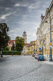 Street scene in Vilnius, Lithuania. VILNIUS, LITHUANIA - OCTOBER 2013: A street scene featuring cobblestone streets and church bell tower in Vilnius, Lithuania Royalty Free Stock Photo