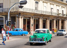 Street scene with vintage american cars in downtown Havana Royalty Free Stock Image