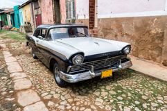 Street scene with vintage car in HTrinidad, Cuba. Royalty Free Stock Images