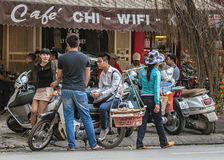 Street scene with young people chatting and food vendor in front Stock Images