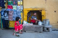 Street seller on the banks of the sacred Ganges river selling selling milk tea - masala. VARANASI, INDIA - MAR 17, 2018: Street seller on the banks of the stock photography
