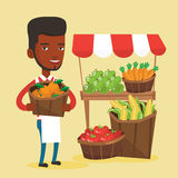 Street seller with fruits and vegetables. An african greengrocer standing near stall with fruits and vegetables. Greengrocer standing near market stall Stock Images