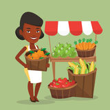 Street seller with fruits and vegetables. An african greengrocer standing near stall with fruits and vegetables. Greengrocer standing near market stall Royalty Free Stock Photo