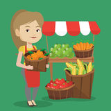 Street seller with fruits and vegetables. Caucasian greengrocer standing near stall with fruits and vegetables. Greengrocer standing near market stall Royalty Free Stock Photography