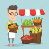 Street seller with fruits and vegetables. Caucasian greengrocer standing near stall with fruits and vegetables. Greengrocer standing near market stall Royalty Free Stock Photos