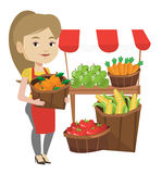 Street seller with fruits and vegetables. Greengrocer standing near stall with fruits and vegetables. Greengrocer standing near market stall. Greengrocer Stock Photos