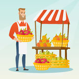 Street seller with fruits and vegetables. Young greengrocer standing near the stall with fruits and vegetables. Greengrocer standing near the market stall Stock Photography