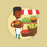 Street seller with fruits and vegetables. Young greengrocer standing near stall with fruits. Greengrocer standing near market stall. Greengrocer holding basket Stock Photo