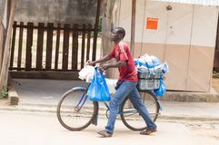 A street seller of plastic bags. In Ivory coast, in the neighborhoods peripherals that sellers are walking bags on their bikes in the streets to sell their Stock Photo