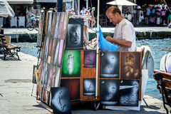 Street seller trading hand made pictures at harbour of Chania town on Crete island Stock Images