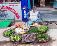 Street seller in Varanasi. A vegetable seller is sitting with his goods in front of a restaurant on the market of Varanasi Royalty Free Stock Photo
