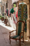 Street with a shop and laundry. Street with a shop, where are dresses hanging on the door and there is a comfortable old style chair. Behind laundry hanging to Royalty Free Stock Photography