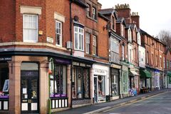 Street Of Shops In Leek, Staffordshire, England. LEEK, UK - DECEMBER 31 2015: A row of small, independent shops occupies the ground floor of historic red brick royalty free stock images