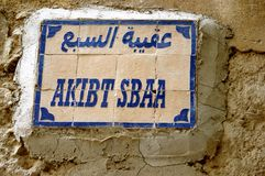 Street sign in Arabic on a wall in the old Fez medina in Morocco. Authentic Arabic street signage cemented to a wall in the old Fez Medina in Morocco.  The Stock Photography