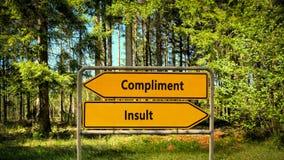 Street Sign Compliment versus Insult. Street Sign the Direction Way to Compliment versus Insult stock photos