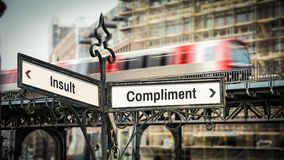 Street Sign Compliment versus Insult. Street Sign the Direction Way to Compliment versus Insult stock photo