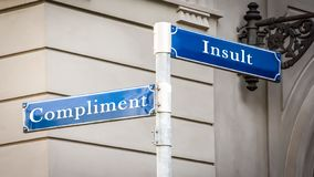 Street Sign Compliment versus Insult. Street Sign the Direction Way to Compliment versus Insult royalty free stock photos