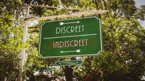 Street Sign Discreet versus Indiscreet. Street Sign the Direction Way to Discreet versus Indiscreet royalty free stock photography