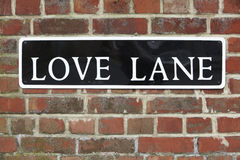 Street Sign For Love Lane On Brick Wall Stock Image