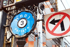 Street sign PATTAYA 3 in English and Thai next to a NO LEFT TURN Stock Image
