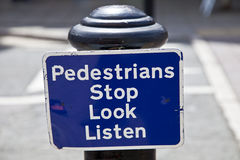 Street sign pedestrians stop look listen Stock Images