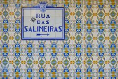 Street sign in Portugal. Blue tiles. Azulejos blue tiles street signs `Rua das Salineiras` on wall on blue and yellow tiles.  Aveiro, Portugal, June 23, 2017 stock image