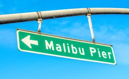 Street sign saying Malibu Pier on a sunny day. Green and white street sign saying Malibu Pier on a sunny day in California Royalty Free Stock Images