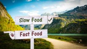 Street Sign Slow versus Fast Food. Street Sign the Direction Way to Slow versus Fast Food stock photo