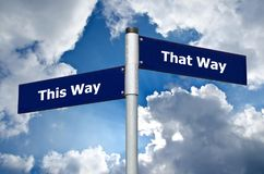 Street sign symbolizing choice between `this way` and `that way`. Street sign in front of cloudy sky symbolizing choice between `this way` and `that way stock photos