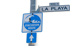 Street sign tsunami evacuation. Street sign at the beach pointing out the evacuation route, isolated Royalty Free Stock Image