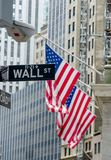 Road sign of wall street against US flag in horizontal view Royalty Free Stock Photo
