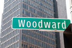 Street sign for Woodward Avenue, a main thoroughfare in the City of Detroit, Michigan. There is a generic office building in the background Royalty Free Stock Photography